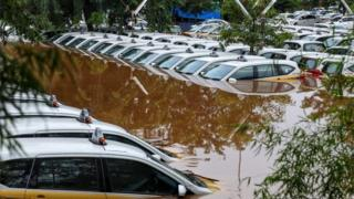 A fleet of flooded taxis are seen at the operator's submerged parking lot following overnight rain in Jakarta on January 1, 2020.